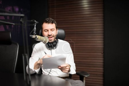 Portrait of young male radio host at radio station with headphones and microphone