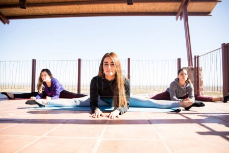 Three young women working on their flexibility and some legs splits in a yoga class