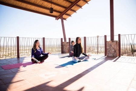 Group of young women sitting on the exercise mat and relaxing in yoga position