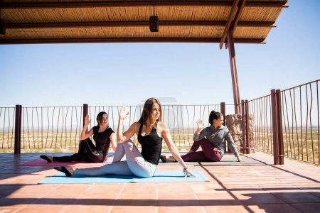 Three young Hispanic women doing the spinal twist yoga pose in a fitness studio