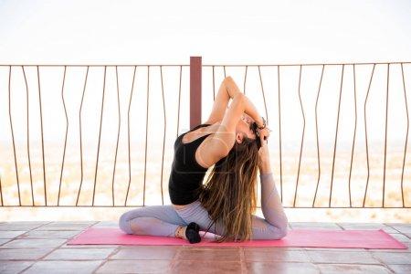 Young woman practicing king pigeon pose at yoga studio