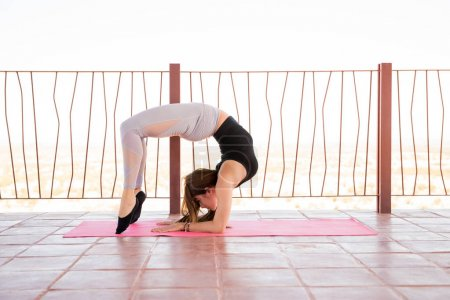Portrait of young woman doing the scorpion pose and maintaining balance during her yoga practice