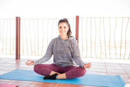 Portrait of attractive young latin woman sitting in easy yoga pose on fitness mat and smiling