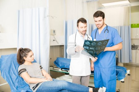 Photo pour Radiologiste discutant des résultats de l'IRM avec un médecin en salle d'urgence avec une patiente au lit - image libre de droit