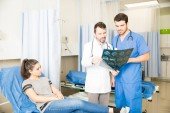 Radiologist discussing at MRI scan results with a doctor in emergency room with female patient on bed