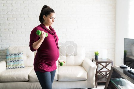 Photo for Determined gorgeous pregnant woman exercising with dumbbells while looking away in living room - Royalty Free Image