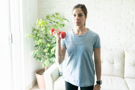 Cute active woman in her 40s doing bicep curls and exercising at home with a pair of dumbbells and smiling