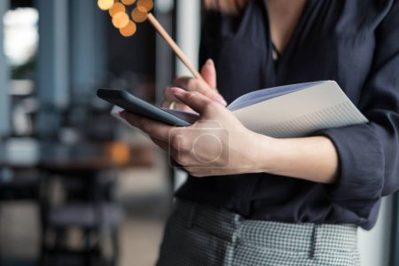 close-up photo of woman in black shirt holding book and mobile at office