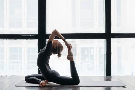 Photo for Young flexible sporty woman practicing yoga near windows on wooden floor - Royalty Free Image