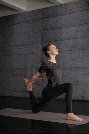 young flexible sporty woman practicing yoga on grey yoga mat on wooden floor