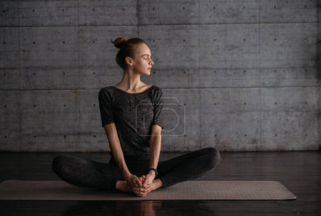 young flexible sporty woman in lotus pose, practicing yoga on grey yoga mat on wooden floor