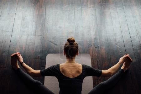 Photo pour Jeune femme sportive souple en bateau Pose, pratiquer l'yoga sur le tapis d'yoga gris sur plancher en bois - image libre de droit