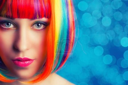 Photo for Beautiful woman wearing colorful wig against blue background - Royalty Free Image