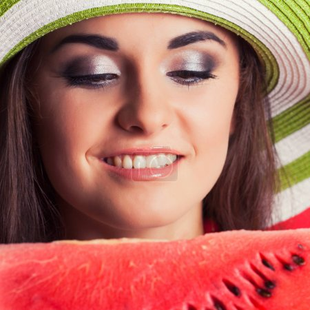 Photo for Beautiful young woman holding watermelon against red background - Royalty Free Image