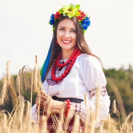 Photo pour Belle jeune femme portant des vêtements nationales ukrainiens, posant dans le champ de blé - image libre de droit