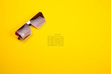 Foto de Elegantes gafas de sol sobre un fondo de papel amarillo - Imagen libre de derechos