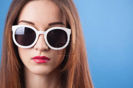 Beautiful young girl wear sunglasses on a blue background