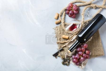 Photo pour Nourriture et boissons, nature morte, vacances récolte saisonnière concept automne. Bouteille, tire-bouchon, bouchons, verre de vin rouge et raisins sur une table en béton tendance. Copier l'espace arrière-plan, vue du dessus plat lay - image libre de droit
