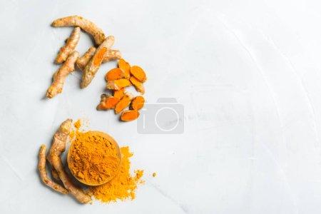 Photo pour Aliments et boissons, alimentation, concept de soins de santé. Racine et poudre de curcuma orange biologique, curcuma longa sur une table de cuisson. Épices orientales indiennes à faible cholestérol. Copier l'espace arrière-plan, vue du dessus - image libre de droit