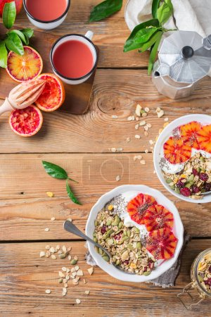 Photo for Healthy food, diet and nutrition concept. Early morning breakfast with homemade granola muesli, natural yogurt, seasonal ripe blood oranges juice. Top view flat lay kitchen wooden background - Royalty Free Image