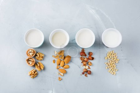 Photo pour Aliments et boissons, soins de santé, régime alimentaire et concept nutritionnel. Assortiment de lait végétalien biologique non journal de noix dans des verres sur une table de cuisine. Vue du dessus fond plat laïc - image libre de droit
