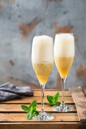 Photo for Food and drink, holidays party concept. Cold fresh alcohol beverage american fizz cocktail in a flute glass with rum, champage, juice and banana on a wooden table - Royalty Free Image