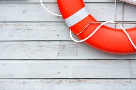 Orange lifebuoy on white wall in port