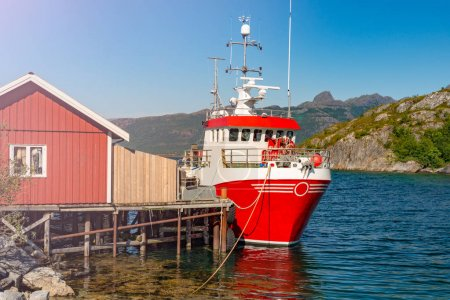 Photo for Tugboat or fishing boat at pier, Norway, Europe. Ship in foreground and blue sky and mountains in background. Scandinavia travel. - Royalty Free Image