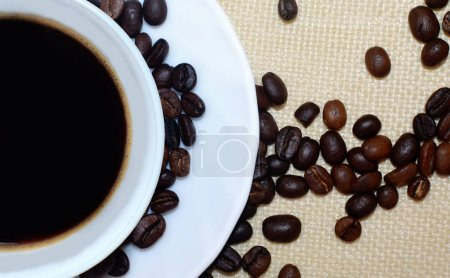 Half of coffee cup and coffee beans on natural linen background. View above. Close up