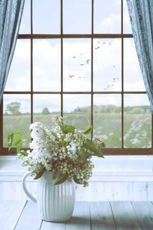Photo for Lilac flowers in vase on a table by the window overlooking country field - Royalty Free Image