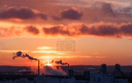 The sun is at dawn. Smoke and roofs of houses. Yekaterinburg, Russia