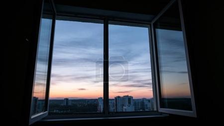 Photo pour Nuages du coucher du soleil à travers une vitre avec une réflexion en l'ouvrant - image libre de droit