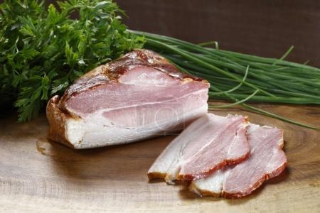 Sliced bacon on wooden board