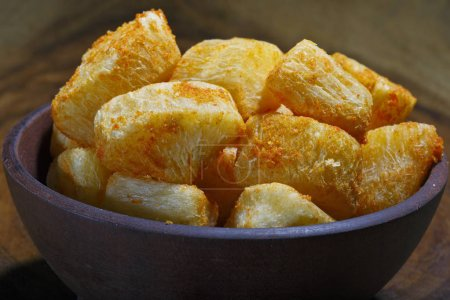 Photo for Cassava, traditional Brazilian food in dark plate, close up view - Royalty Free Image