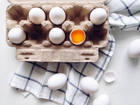 Photo pour Oeufs bio blancs en paquet sur une table de la cuisine, vue de dessus de jaune d'oeuf oeufs - image libre de droit
