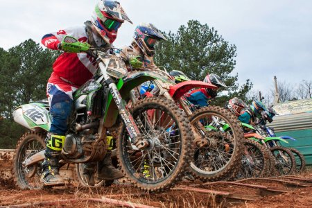 Motocross Riders Lunge Forward At