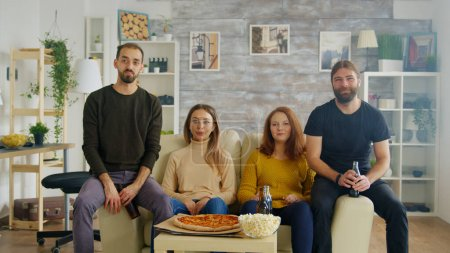 Photo pour Groupe d'amis dégustant une délicieuse pizza tout en socialisant et en regardant des sports à la télévision. - image libre de droit