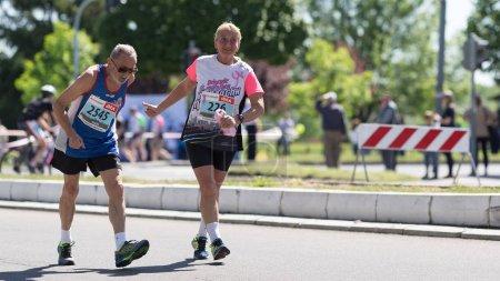 Elderly man and woman running marathon, encouraging each other