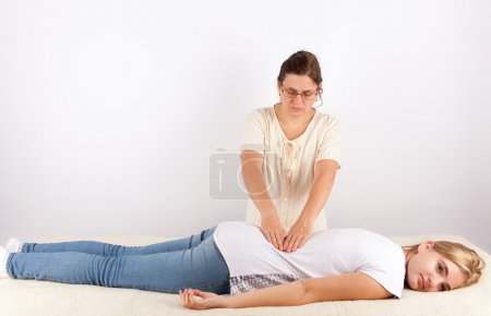 Young woman receives bowen treatment for her back ...