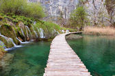 Wooden tourist path goes trhough waterfalls in Plitvice Lakes Na