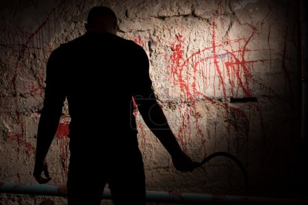 Shadowy figure near blood stained wall