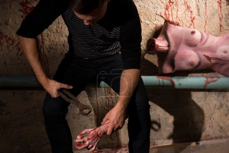 Male sitting on the pipe with a bloody torso of a dead woman on
