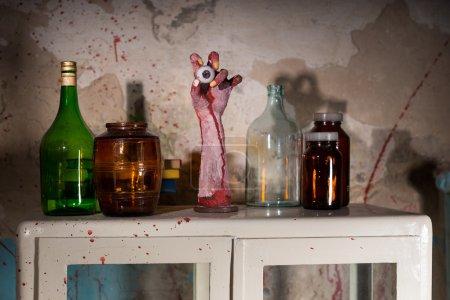 Photo pour Main amputée avec globe oculaire entre les pots de verre avec mur éclaboussures de sang séché - image libre de droit