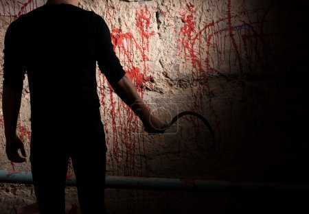 Shadowy male figure near blood stained wall