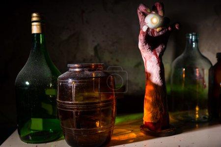 Photo pour Gros plan de main ridée avec globe oculaire entre les pots de verre avec mur éclaboussures de sang dans un concept d'horreur Halloween - image libre de droit