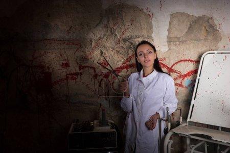 Female scientist holding large iron scissors in dungeon
