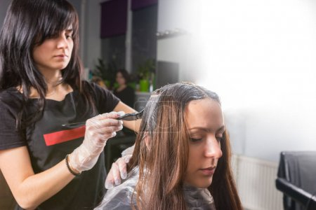 Attractive brunette female stylist stands and dyeing hair of you