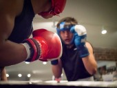 Amateur boxer loading up a punch, rear view