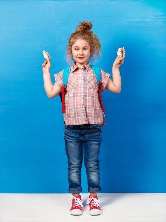 Photo pour Portrait d'enfant blonde avec coquillages au mur bleu. Concept vacances d'été . - image libre de droit