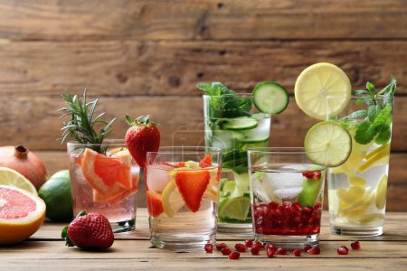 Lemonades with lemons, cucumbers, limes, grapefruits, strawberries, mint leaves and garnet seeds served on wooden table.